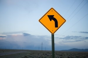 Highway sign showing curve ahead - blurred background.